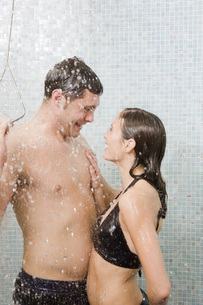 Couple in bathing suits taking showerの写真素材 [FYI01997722]