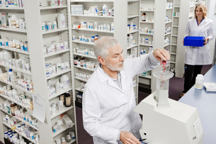 Pharmacist pouring pills into counting machineの写真素材 [FYI01997728]