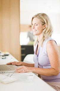 Woman using laptop in home officeの写真素材 [FYI01997738]