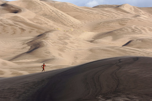Person running on sand dunesの写真素材 [FYI01997748]