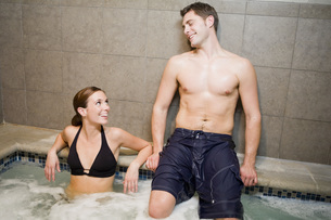 Couple smiling at each other in hot tubの写真素材 [FYI01997756]
