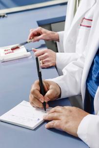Close up of pharmacist writing on prescription padの写真素材 [FYI01997772]