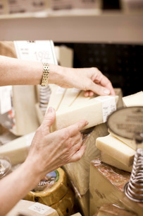 Woman selecting cheese in grocery storeの写真素材 [FYI01997790]