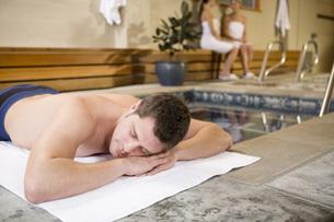 Man laying next to hot tubの写真素材 [FYI01997803]