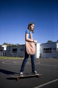 Girl riding long skateboard in school yardの写真素材 [FYI01997809]