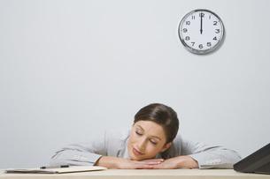 Businesswoman resting head on deskの写真素材 [FYI01997812]