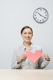 Businesswoman holding cut-out heartの写真素材 [FYI01997823]