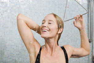 Woman in bathing suit taking showerの写真素材 [FYI01997825]