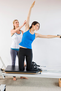 Personal trainer guiding woman on pilates equipmentの写真素材 [FYI01997929]