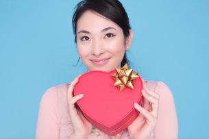 ハート形のプレゼントを持った女性の写真素材 [FYI01997936]