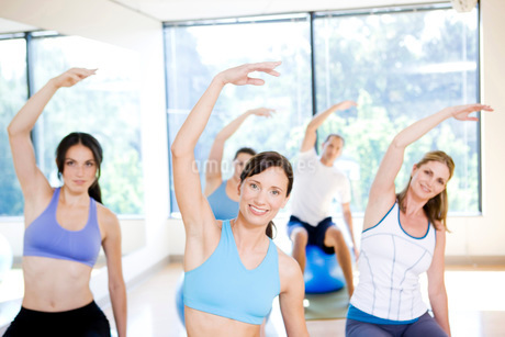 Portrait of people with arms raised in exercise classの写真素材 [FYI01997976]