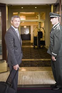 Businessman and bellhop in hotel doorwayの写真素材 [FYI01997980]
