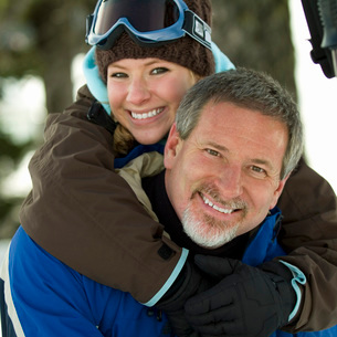 Father and daughter in ski gear huggingの写真素材 [FYI01998026]