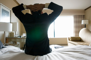 Businessman sitting on bed in hotel roomの写真素材 [FYI01998059]