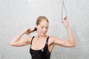Woman in bathing suit taking showerの写真素材 [FYI01998061]