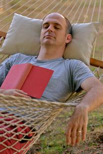 Man sleeping in hammockの写真素材 [FYI01998062]