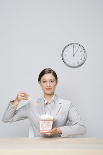 Businesswoman eating take out foodの写真素材 [FYI01998067]