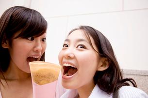 友達のクレープを食べようとする女性の写真素材 [FYI01998070]