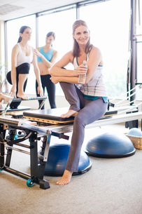 Portrait of smiling woman on pilates equipmentの写真素材 [FYI01998097]