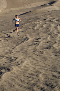Woman running on sand dunesの写真素材 [FYI01998099]