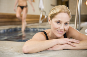 Young woman leaning of edge of hot tubの写真素材 [FYI01998163]
