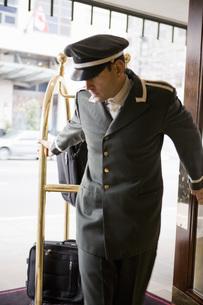 Bellhop pulling luggage cartの写真素材 [FYI01998313]