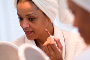 African woman applying makeupの写真素材 [FYI01998370]
