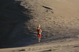 Woman running on sand dunesの写真素材 [FYI01998441]