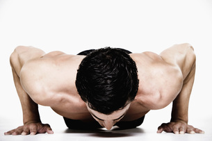 Bare-chested man doing push-upsの写真素材 [FYI01998471]