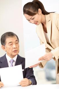 社長に資料の説明をする秘書の写真素材 [FYI01999002]