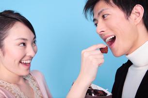チョコレートを男性に食べさせる女性の写真素材 [FYI01999035]
