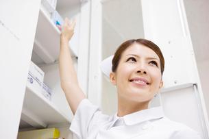 棚から物を取ろうとする看護師の写真素材 [FYI01999037]