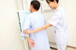 レントゲンをとる患者の腕を支える女性技師の写真素材 [FYI01999106]