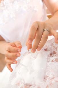 リングピローから指輪を外す新婦の手元の写真素材 [FYI01999259]