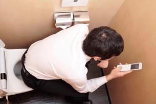 トイレでメールするサラリーマンの写真素材 [FYI01999287]