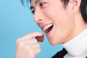 チョコを食べようとする男性の口元の写真素材 [FYI01999373]