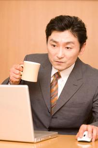 パソコンを見ながらコーヒーを飲むビジネスマンの写真素材 [FYI01999387]