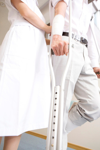 松葉杖をつく男性患者とフォローする看護師の写真素材 [FYI01999410]
