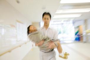 娘を抱えて病院に連れてきた父親の写真素材 [FYI01999519]