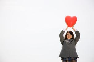ハートの風船を掲げる女子高生の写真素材 [FYI01999701]