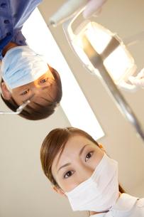 患者を覗き込む男性歯科医と歯科衛生士の写真素材 [FYI02000009]