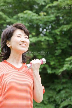 公園でダンベルを持ち筋トレしているシニア女性の写真素材 [FYI02000026]