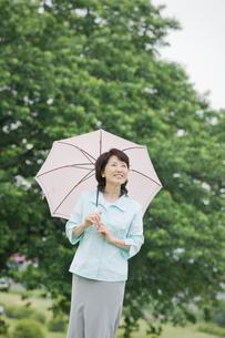 日傘をさしながら公園を散歩するシニア女性の写真素材 [FYI02000181]