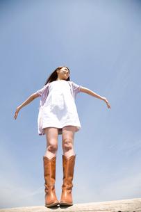 丸太の上に立って両手を広げる女性の写真素材 [FYI02000218]