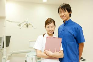 治療台の前に立つ男性歯科医と歯科衛生士の写真素材 [FYI02000231]