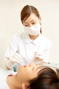 歯科衛生士と治療を受ける男性の写真素材 [FYI02000267]