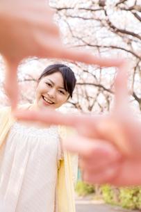 桜をバックに指のフレームの中で微笑む女性の写真素材 [FYI02000313]