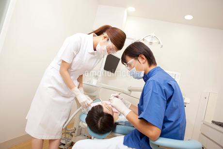 女性患者の治療をする男性歯科医と歯科衛生士の写真素材 [FYI02000387]