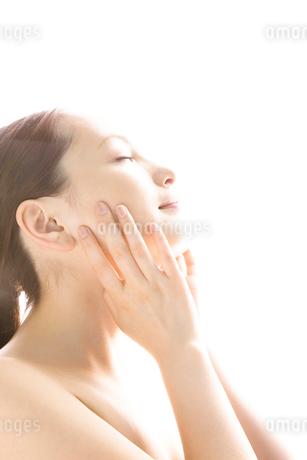 手を頬にあてている女性の写真素材 [FYI02000421]