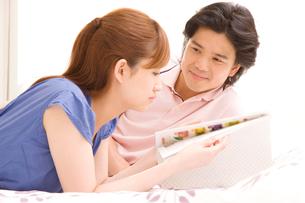 ベッドの上で雑誌を読むカップルの写真素材 [FYI02000424]